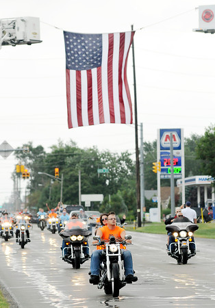Don Knight   The Herald Bulletin<br /> Jessica and Lynsey Memorial Ride passes under an American flag while traveling on 53rd Street on Saturday. Proceeds benefit scholarships in memory of Jessica Lyons and Lynsey Schildmeier.