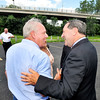 John P. Cleary | The Herald Bulletin<br /> Madison County Engineer Chuck Leser and U.S. Senator Joe Donnelly greet each other with the Eisenhower Bridge in the background. Leser has worked for years on getting federal money to help replace the aging bridge. Donnelly was in town with county and city leaders to highlight the federal grant to replace Eisenhower Bridge the county has received.