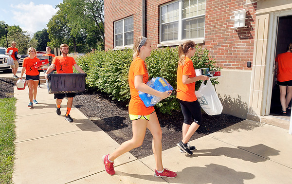 John P. Cleary | The Herald Bulletin<br /> A parade of orange shirted AU volunteers carry items into Smith Hall for the new freshmen coming to campus on move-in day for the university.