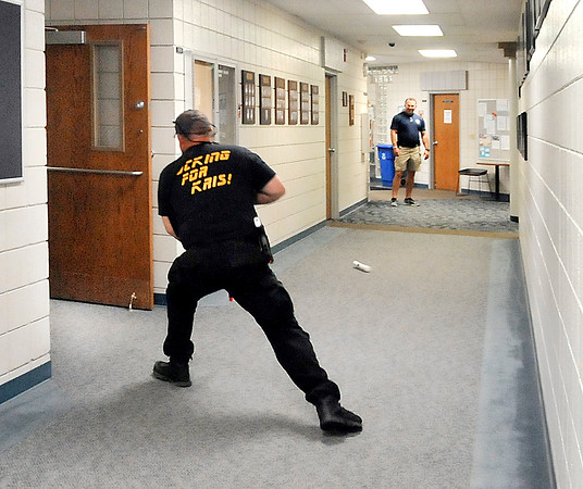 John P. Cleary   The Herald Bulletin<br /> Training instructor Jamie Hodge, backgound, watches as an officer reacts to seek cover as an IED is tossed in his direction during police training being held at Ivy Tech at 104 W. 53rd St.
