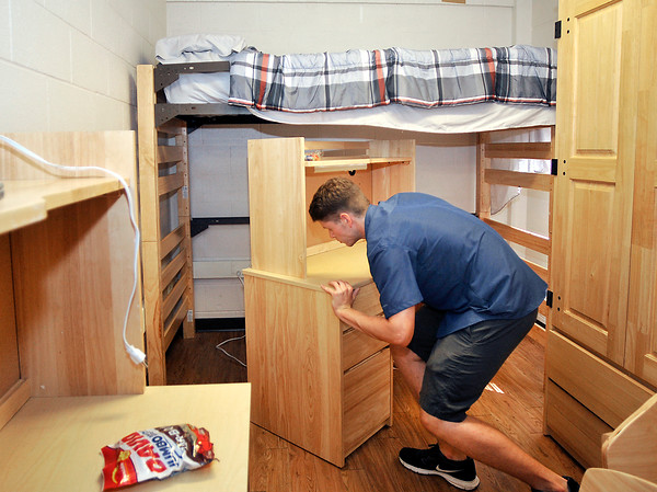 John P. Cleary   The Herald Bulletin<br /> Incoming Anderson University freshman Wesley Busby, from Pendleton, re-arranges the furniture in his dorm room at Smith Hall Thursday during move-in day for the 475 freshman and transfer students coming to AU.