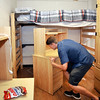 John P. Cleary | The Herald Bulletin<br /> Incoming Anderson University freshman Wesley Busby, from Pendleton, re-arranges the furniture in his dorm room at Smith Hall Thursday during move-in day for the 475 freshman and transfer students coming to AU.