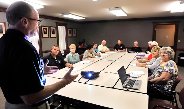 John P. Cleary | The Herald Bulletin<br /> APD detective Mark Brizendine, of Community Oriented Policing Services, talks to volunteers for the Senior Link-Are You OK? program.