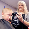 John P. Cleary | The Herald Bulletin<br /> Billie Surface, 5, doesn't seem thrilled as he receives a back-to-school haircut from Dawn Moree at the Back-to School Rally for Alexandria students held this past week. Billie will be a kindergartner at Alexandria-Monroe Elementary School.