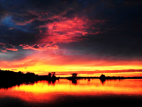 Don Knight | The Herald Bulletin<br /> A break in the weather Sunday evening made for a beautiful sunset on Summit Lake in Henry County. The rain returned Monday and daily rain chances are forecast for the rest of the week.