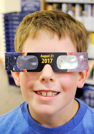 Don Knight | The Herald Bulletin<br /> Scott Foga, 9, tries on his eclipse glasses he got from the Anderson Public Library after visiting the Dome Theater, a mobile planetarium, on Thursday.