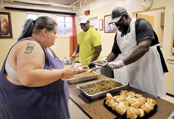 John P. Cleary |  The Herald Bulletin<br /> Krista Petersen gets served by Jonathan Jackson, right, as Senior Pastor Louis Jackson Jr., center, looks on during the churches first monthly dinner held July 12th. The church will hold dinners on the second Wednesday of each month.