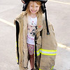 Don Knight | The Herald Bulletin<br /> Chloe Crabtree, 6, tries on a AFD turnout coat and helmet during a St. Jude Benefit at Northgate True Value on Saturday.