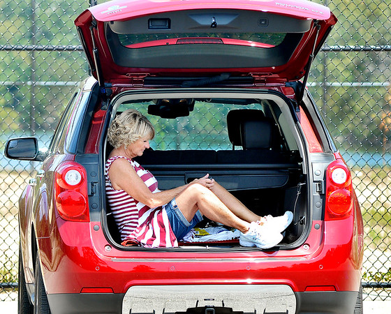 John P. Cleary    The Herald Bulletin<br /> Linda Bush, of Anderson, checks her messages as she relaxes in the back of her SUV after doing her workout walk around the Shadyside Park trails Monday afternoon.