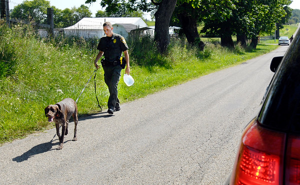 John P. Cleary    The Herald Bulletin<br /> An Indiana DNR conservation officer leads his K9 partner along County Road 1400 North Wednesday morning as officers were searching the area near Ind. 9 for more evidence related to a shooting earlier in the day where a man was found shot with nine gunshot wounds.