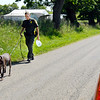 John P. Cleary |  The Herald Bulletin<br /> An Indiana DNR conservation officer leads his K9 partner along County Road 1400 North Wednesday morning as officers were searching the area near Ind. 9 for more evidence related to a shooting earlier in the day where a man was found shot with nine gunshot wounds.