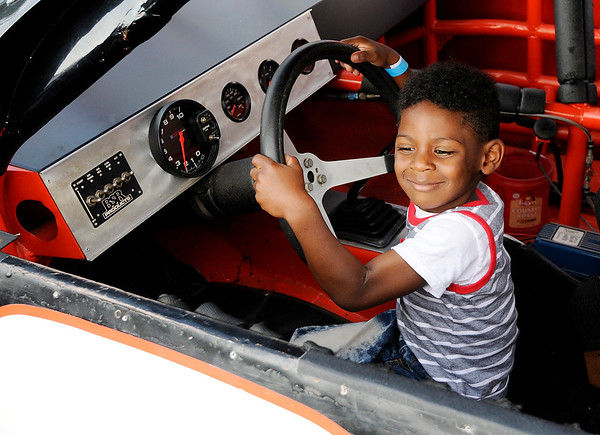 Don Knight | The Herald Bulletin<br /> Greg Burton, 5, sits in race car during the Madison County Community Health Center's annual Back Yard BBQ on Friday. Next week is National Health Center Week.