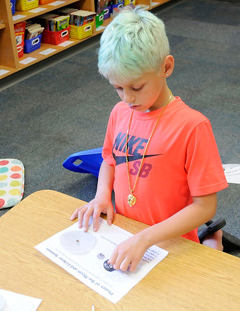 Don Knight   The Herald Bulletin<br /> Dexton Hitchens, 9, creates a model of the earth, moon and sun as Pamela Kittle's fourth grade class learns about the solar eclipse on Friday.