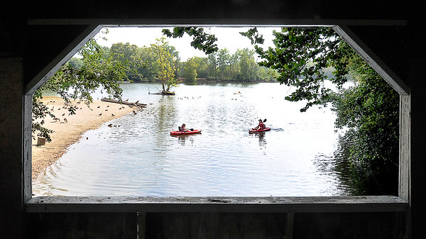 John P. Cleary    The Herald Bulletin<br /> Framed by the window of the covered bridge Shelby Cruea and sister Stormie Cruea paddle around the south end of the channel at Shadyside Park Monday as they were enjoying the afternoon on a family outing of boating and fishing. The Crueas are from Middletown.