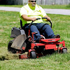 John P. Cleary |  The Herald Bulletin<br /> Jimmy Vest cuts a path through the tall grass as he mows this lot on North E Street in Elwood this past Tuesday. Vest, a part-time landscaper, was hired by the city to mow neglected properties around Elwood.