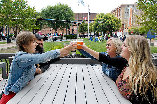 John P. Cleary |  The Herald Bulletin<br /> Taylor Cleveland, Ross Cleveland, Teena Hopkins, and Emily Clark raise their glasses for a toast as they celebrate a birthday Friday evening on the patio of  Kettletop Brewhouse in downtown Anderson as a concert goes on at Dickmann Town Center.