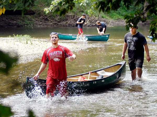 John P. Cleary |  The Herald Bulletin<br /> Members of the Frankton football team bring their canoes up to the ramp at Mounds State Park Friday afternoon to end their day competing in a White River cleanup with the Lapel football team.