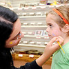 Don Knight | The Herald Bulletin<br /> Rio Santos paints a peace symbol on Lila Marr's cheek during the Kids Kones Dogs & Bones event at Good's Candy Shop on Saturday.