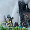 Don Knight | The Herald Bulletin<br /> AFD firefighters attack a blaze in the 900 block of East 10th Street on Tuesday.