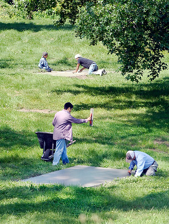 John P. Cleary    The Herald Bulletin<br /> Workers from Bautista Landscaping smooth out the freshly poured concrete of the pads for the new disc golf course being built at Edgewater Park this past weekend. According to Levi Rinker, barring any weather issues over the next few weekends, the volunteer help should have the course completed and ready for play in early September.
