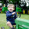 John P. Cleary |  The Herald Bulletin<br /> Little Avery Forgus, 1, of Anderson, shows off his tractor at the antique tractor show at the Markleville Jamboree Friday evening.