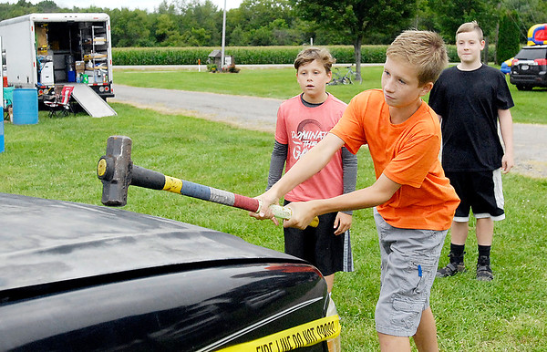 John P. Cleary |  The Herald Bulletin<br /> As his friends watch, Trenton Gustin, 12, takes a big whack at a wreck during the Markleville Jamboree Friday evening. The preceeds raised from the event  will go to the Hoosier Burn Camp.