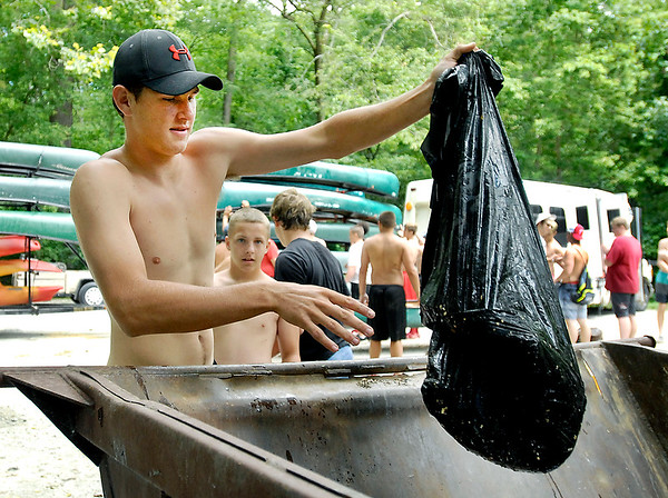 John P. Cleary    The Herald Bulletin<br /> Frankton High School football player Will Whatley dumps a bag of trash he collected while canoeing down White River Friday. The Frankton team competed against the Lapel football team in a river cleanup project.