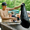 John P. Cleary |  The Herald Bulletin<br /> Frankton High School football player Will Whatley dumps a bag of trash he collected while canoeing down White River Friday. The Frankton team competed against the Lapel football team in a river cleanup project.