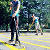 John P. Cleary | The Herald Bulletin<br /> Anderson University summer maintenance employees Noah Miller, and Troyer Goldman put a fresh coat of paint on the yellow lines in the no parking area between Byrum Hall and Olt Student Center Monday. They were getting parking lines and curbs repainted in preparation for the start of fall classes later this month.