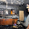 John P. Cleary | The Herald Bulletin<br /> Jason Boggan looks over what is left of the kitchen after a house fire at 1225 Home Ave. displaced his sister-in-law, Edna Hammons, and her four children. Hammons and her children are now living with the Boggans.