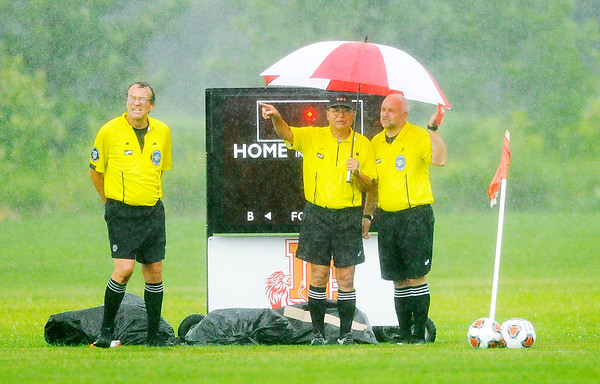 Don Knight | The Herald Bulletin<br /> Game officials look toward the west at a clearing horizon as a brief heavy downpour moved through before Liberty Christians' game against Muncie Burris at Davis Park on Tuesday.