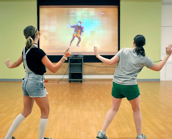 John P. Cleary | The Herald Bulletin<br /> Emma Verde and Liz Osisek, Teen Services Librarian, follow the dance moves they see on the screen as they get their groove on at the Just Dance Party! event Tuesday at the Anderson Public Library.