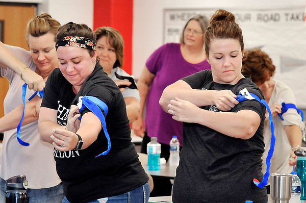 John P. Cleary | The Herald Bulletin<br /> Cera McCord and Meghan Hersberger, both first-grade teachers at Frankton Elementary School, practice putting a tourniquet on themselves as fast as they can as they go through a school safety training session for teachers and staff of Frankton/Lapel Schools.<br /> <br /> <br /> <br /> Teachers and staff of Frankton/Lapel Schools attend a school safety training session titled: Preventing the Preventable Death.