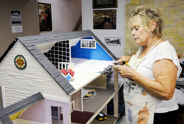 Don Knight   The Herald Bulletin<br /> Diana Pine renovates a dolls house that will be part of an upcoming exhibit at the Madison County Historical Society. The Society has asked the county for $15,000 to help cover their utility expenses.