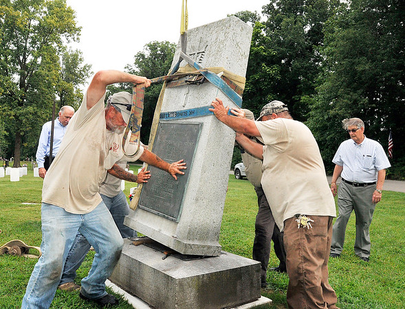 John P. Cleary | The Herald Bulletin<br /> Maplewood Cemetery workers maneuver the Anderson High School World War I monument into place at it's new home in the Veterans section of Maplewood Cemetery Monday morning. The Kikthaweund DAR Chapter along with Maplewood Cemetery worked together to raise the funds and coordinate the move of the monument from it's spot on the lawn of the former Anderson High School site to the new location.