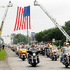 Don Knight | The Herald Bulletin<br /> Motorcycles travel west on 53rd Street past Fire Station 8 and a large flag displayed by the Anderson Fire Department during the the 13th annual Jessica & Lynsey Memorial Ride on Friday. The ride remembers Jessica Lyons and Lynsey Schildmeier, best friends who were killed seven years apart.