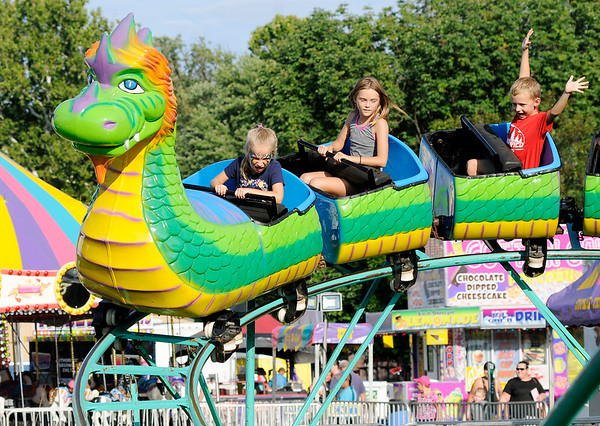 Don Knight | The Herald Bulletin Kids ride a roller coaster in the midway at Callaway Park during the Elwood Glass Festival on Friday. The festival continues through Sunday. You can find a schedule of events at elwoodglassfestival.com.