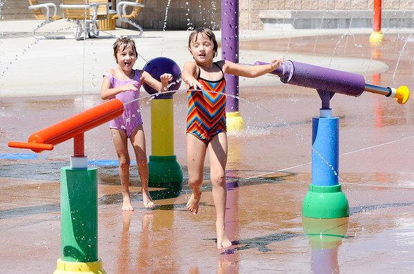 Don Knight | The Herald Bulletin<br /> From left, twins Elise and Adelaide Ellcessor play at the splash pad in Daleville on Wednesday. The forecast for Thursday is calling for a brief break from the heat before it builds back in for the holiday weekend.