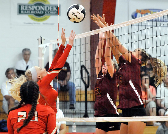 John P. Cleary | The Herald Bulletin<br /> Liberty Christian's Savannah Rees tips the ball over the net as Alexandria's Makenzie Adams and Taylor Stinefield try to block.
