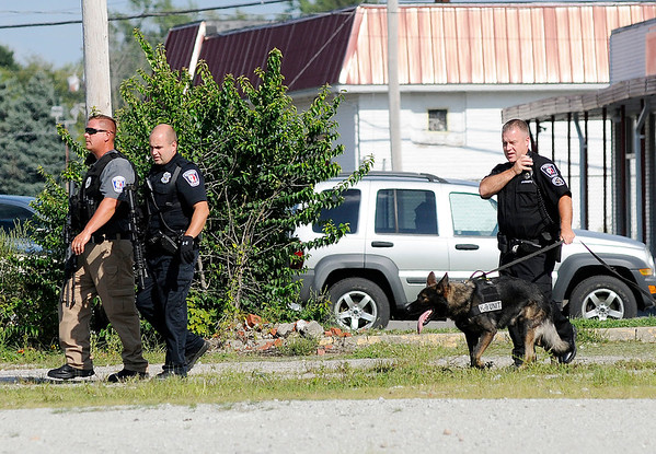 Don Knight | The Herald Bulletin<br /> APD officers move north after searching the area east of Family Dollar with a K9 on Thursday.