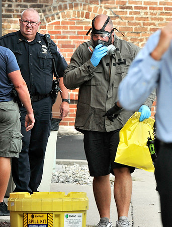 John P. Cleary | The Herald Bulletin<br /> Two APD officers were packaging evidence and was exposed to an unknown substance. Hazmat was called in. Here an officer brings out a bag containing the unknown substance wearing a breathing mask and gloves to secure in a spill kit outside of APD.