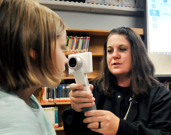 John P. Cleary | The Herald Bulletin<br /> Alexandria-Monroe Elementary School nurse Brittney Gideon, right, takes a photo of second-grader Gabrielle Wise, 7, eye to transmit to a nurse at the Jane Pauley Center during a demonstration Tuesday of the school's new telehealth clinic.