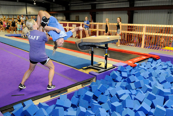 Don Knight | The Herald Bulletin<br /> MEKS Gymnastics Academy co-owner and head coach Misty Carpenter spots her daughter Myleigh Carpenter, 12, as she does a double back flip into a foam pit during an open gym at MEKS as part of their grand opening at their location at 1735 West 53rd Street Building 6 on Saturday.