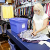 Don Knight | The Herald Bulletin<br /> Mary Ann Mudd prepares donations that have been sorted and laundered to be hung on the racks at Outfitters in Pendleton.