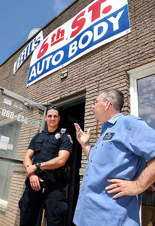 John P. Cleary | The Herald Bulletin<br /> Anderson police officer Sean Brady stops by 6th Street Auto Body to talk with  owner Bill Thompson.