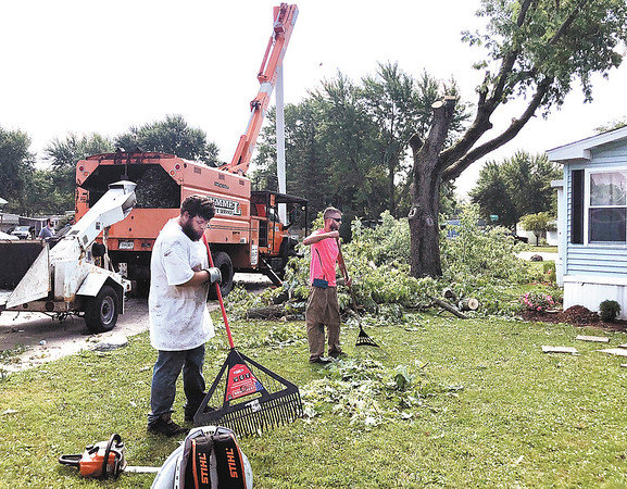 Traci Miller | The Herald Bulletin<br /> Hummel Tree Service employees work to clean up trees and limbs downed at Redbud Estates during the weekend storms. Reports of trees being damaged by high winds and numerous power outages were reported in Madison County following the storms.