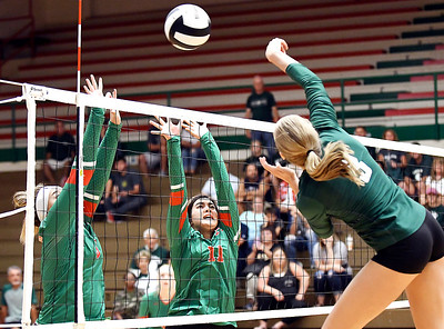 John P. Cleary | The Herald Bulletin Pendleton Heights's Avery Ross, right, gets one of her 10 kills by Anderson defenders Lauryn Williams and Eliana Munoz.