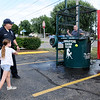 Don Knight | The Herald Bulletin<br /> Breyanna Wagner, 8, sends David Pollard into the dunk tank as Chesterfield Police and Fire PIO Todd Harmeson looks on during National Night Out on Tuesday.