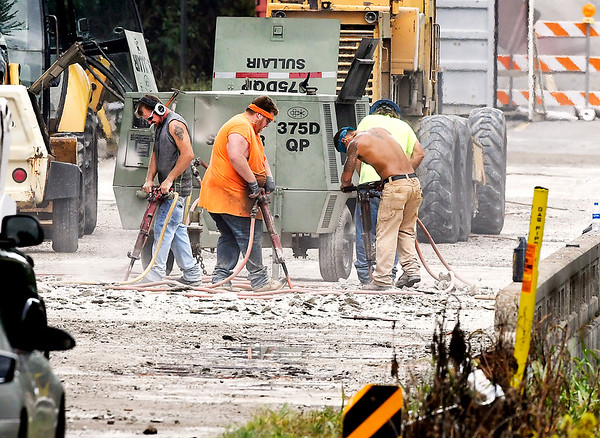 John P. Cleary | The Herald Bulletin<br /> Workers bust up the bad concrete on the bridge deck of the County Road 400 East bridge over White River Tuesday afternoon. The road, closed last week, will be shut down over the river just north of Chesterfield for the next month as workers patch the bad spots and then overlay the entire service with new concrete.