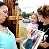John P. Cleary | The Herald Bulletin<br /> Brandy Neff fights back tears as her18-month granddaughter Briar Kumkoski points to the photo of her daddy, Chase Kumkoski, while being held by Aspen Walker, Chase's girlfriend. They were at 25th and Raible Avenue Monday evening next to a memorial cross for Chase who was killed in a motorcycle accident at the intersection three weeks ago.